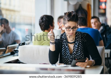 Hip young woman reading a book in coffee shop - stock photo