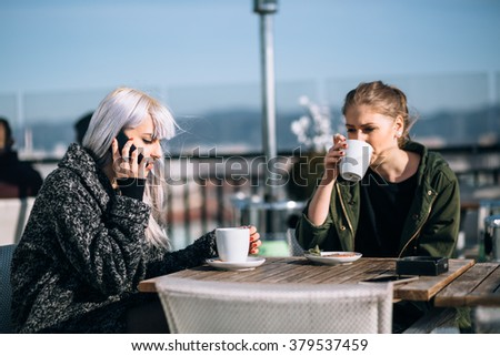 Hip young woman talking on phone in roof top cafe - stock photo