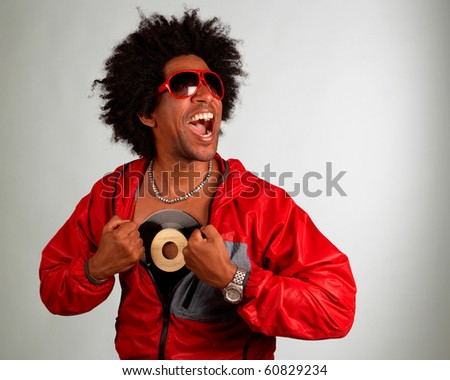 Hiphop artist posing with a vinyl record - stock photo