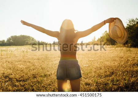 Hippie girl in nature, holding hat looking at Sun - stock photo