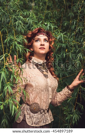 Hippie girl standing under the willow tree ruffling long red curling hairs. Decorations in favorable hippies. style, bracelet, trinket, bauble, chaplet, beads. Vertical. Image released