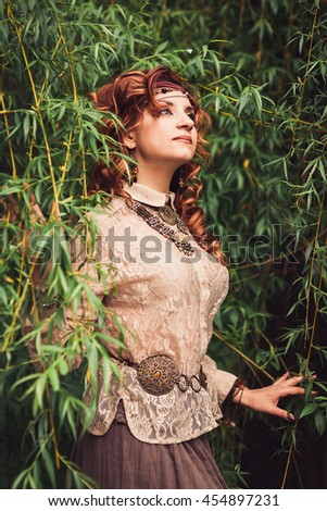 Hippie girl standing under the willow tree ruffling long red curling hairs. Decorations in favorable hippies?? style, bracelet, trinket, bauble, chaplet, beads. Vertical. Image released