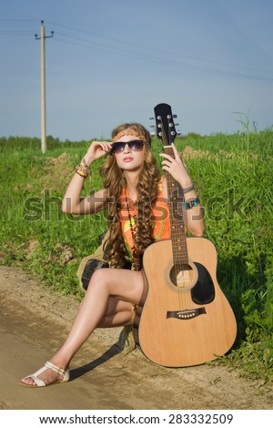Hippie girl traveling with her guitar on a road - stock photo