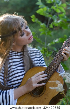 Hippie girl with a guitar  - stock photo