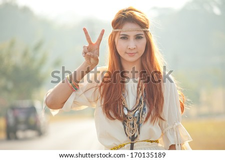 Hippie girl with peace signs in golden field - stock photo