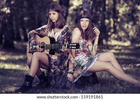 Hippie girls with guitar in a summer forest - stock photo