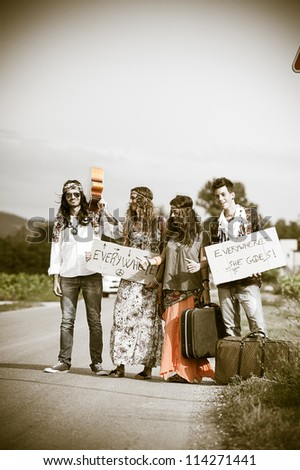 Hippie Group Hitchhiking on a Countryside Road,Italy - stock photo