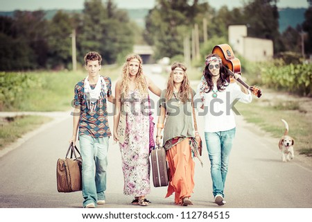 Hippie Group Walking on a Countryside Road,Italy - stock photo