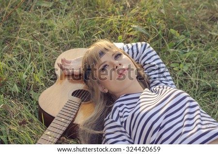 Hippie-style girl posing with a guitar on a hot summer evening, she is wearing a head band, stripy frock and skinny jeans - stock photo