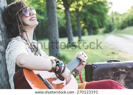 Hippie woman playing guitar - stock photo