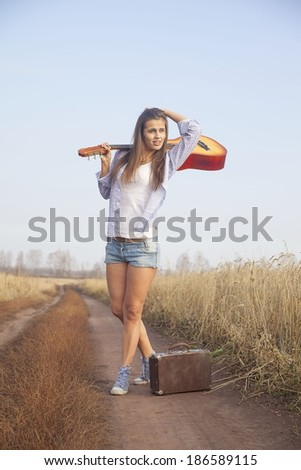 hippie Woman walking in golden wheat field with acoustic Guitar on his shoulder and old retro suitcase in the other hand - stock photo