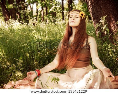 Hippie yoga girl in meditation in the forest - stock photo