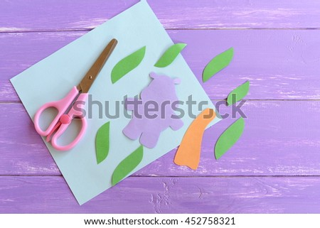Hippo, leaves, palm tree trunk cut from colored paper. Set to create a summer children cards. Scissors, paper sheet. Hippopotamus and palm tree applique crafts arts idea for kids  - stock photo