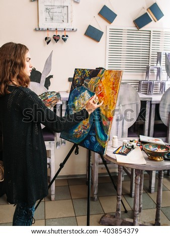 Hipster artist paints a colorful abstract painting. Closeup of painting process in art workshop. Creative hipster woman painter paints in her studio abstract colorful picture.  - stock photo