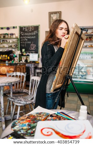 Hipster artist paints a painting in defocused cafe interior. Closeup of painting process in light art workshop interior. Creative  studious hipster woman painter paints in her studio picture.  - stock photo