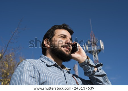 Hipster at phone near to antenna. - stock photo