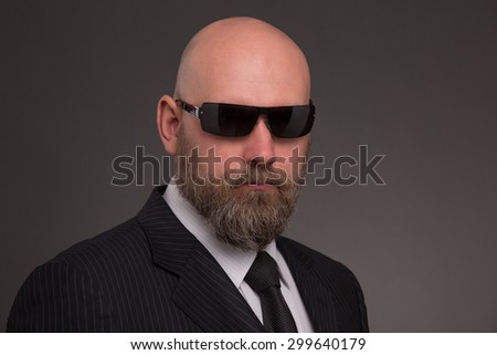 Hipster bearded man poising in black sunglasses. Bold man in business suit looking so serious and demanding on dark grey.