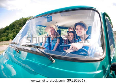 Hipster boy driving an old campervan with teenagers, roadtrip - stock photo