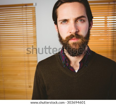 Hipster businessman frowning at camera in his office - stock photo