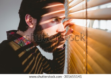 Hipster businessman peeking through blinds in his office - stock photo