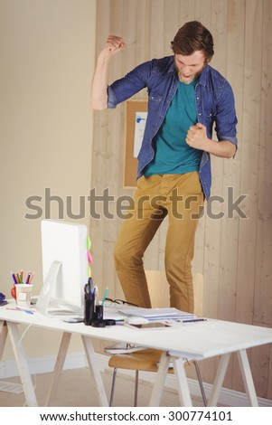 Hipster businessman standing on his chair in his office