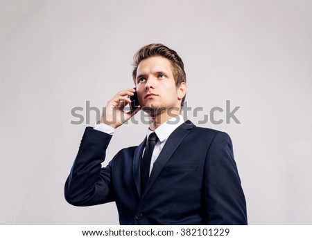 Hipster businessman with smartphone making phone call. Studio sh