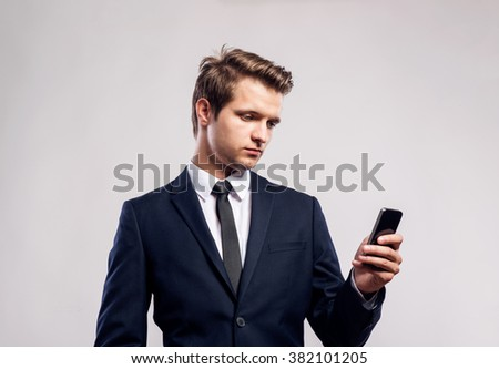 Hipster businessman with smartphone writing text message. Studio