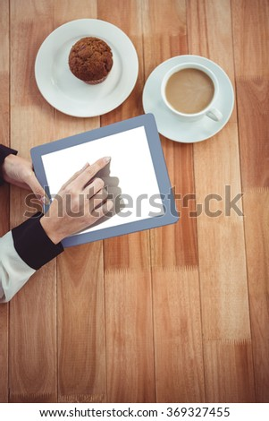 Hipster businesswoman using her tablet on wooden desk