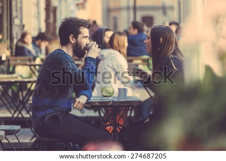 Hipster couple drinking coffee in Stockholm old town. They're sitting face to face. The man is wearing a blue sweater and the woman a striped shirt with black leather jacket. See-through shot. - stock photo