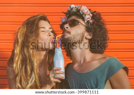 Hipster couple drinking milk from bottle, going crazy and having great time together. Terracotta urban wall background. - stock photo