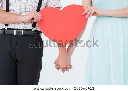 Hipster couple holding heart card on white background