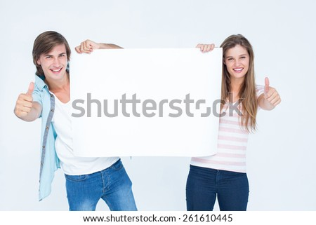 Hipster couple holding poster on white background