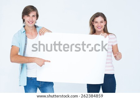 Hipster couple holding poster on white background - stock photo