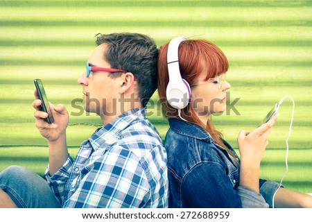 Hipster couple in disinterest moment with mobile phones - Concept of apathy sadness and isolation using new technologies - Boyfriend and girlfriend with smartphones addiction - Vintage filtered look - stock photo