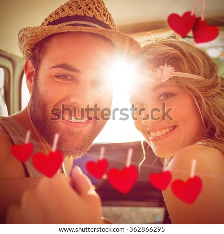 Hipster couple on road trip against hearts hanging on a line - stock photo