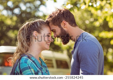 Hipster couple smiling at each other on a summers day - stock photo