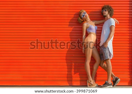 Hipster couple wearing stylish bright outfits and glasses, going crazy and having great time together. Terracotta urban wall background.