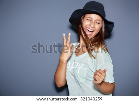Hipster fashionable young woman giving a playful V-sign gesture as she laughs and jokes with the camera in her trendy hat, over grey with copyspace - stock photo