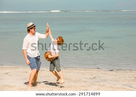 Hipster father with beard and red haired son playing on the beach at the summer day. Vacation, happy and friendly family, holidays concept - stock photo