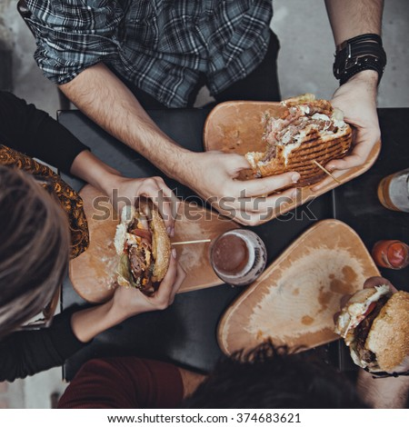 Hipster Friends In Fast Food Restaurant Eating Burgers. View From Above - stock photo
