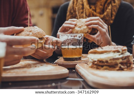 Hipster Friends In Fast Food Restaurant. Focus Is On Beer - stock photo
