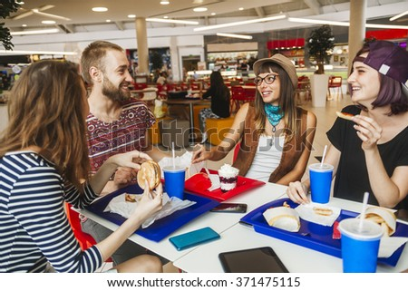 Hipster Friends In Mall Eating Fast Food - stock photo