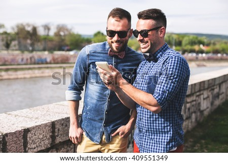 Hipster friends using their phones on a summer's day. Depth of field, focus on man's hand, focus on a hand holding phone - stock photo