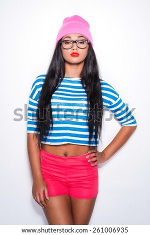 Hipster girl. Attractive young African woman in funky clothes holding hand on hip and looking at camera while standing against white background - stock photo