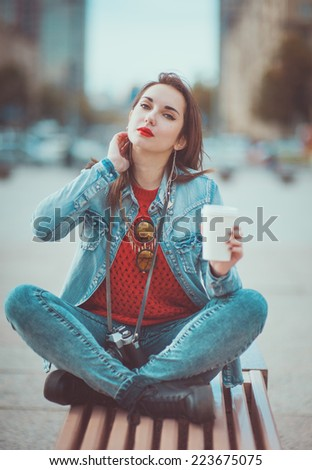 Hipster girl drinking coffee in the city - stock photo