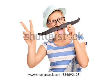 Hipster girl holding fake mustache on her face and making a peace hand sign isolated on white background - stock photo