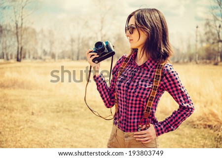 Hipster girl holds photo camera outdoor - stock photo