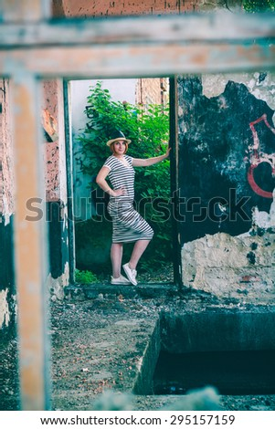 Hipster girl in a hat on the ruins of the old railway station