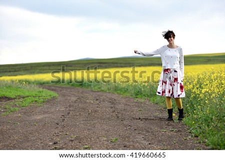 Hipster girl in dress hitchhiking near a countryside road - stock photo