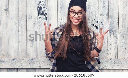 Hipster girl in glasses and black beanie on the wooden background - stock photo